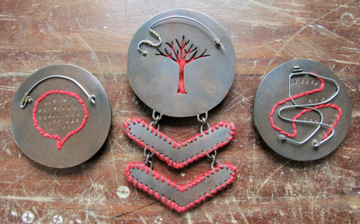 Backs of all three brooches.  (Left)  Famous Last Words... It's a boy scout trail.  How long can it be.  (Center)  Tar Hollow - Red Blazes.  (Right) Tar Hollow Fire Tower - Best View... of just how lost we are